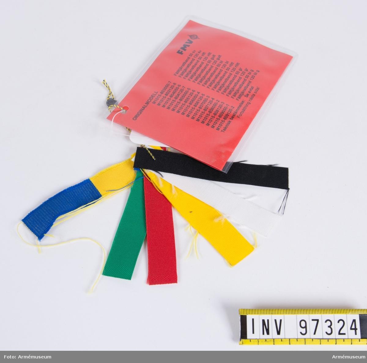 Knippe med prov på band i olika färger. Varje färg har eget M-nummer. På den vidhängande modellappen anges alla M-nummer samt att teknisk bestämmelse finns i avtalet. Lappen är underskriven 1999-01-14 av Roger Strömstedt.