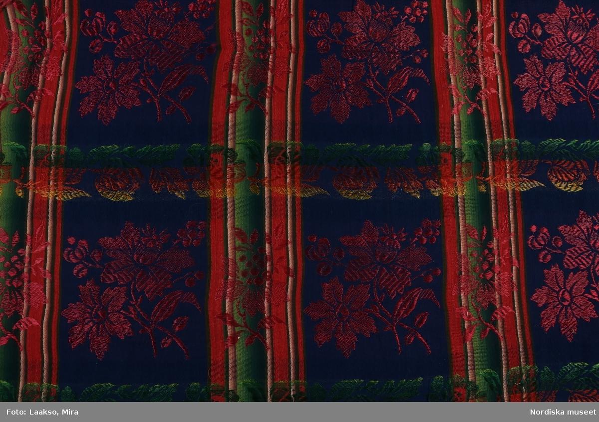 Kvadratiskt halskläde av halvsiden med mörkblå botten i bomullssatin indelad i stora rutor med bårder i varpriktningen i grönt, rött beige, brunt och i inslagsriktningen med jacquardvävda bladbårder i grönt, rosa och gult silke. I varje ruta en stor blomkvist i starkrosa silke.  2 tråcklade fållar, iknuten gles frans av rosa otvinnat silke.  I fint skick.  Samma mönster i något annorlunda färgskala se inv.nr  559. /Berit Eldvik 2012-01-09