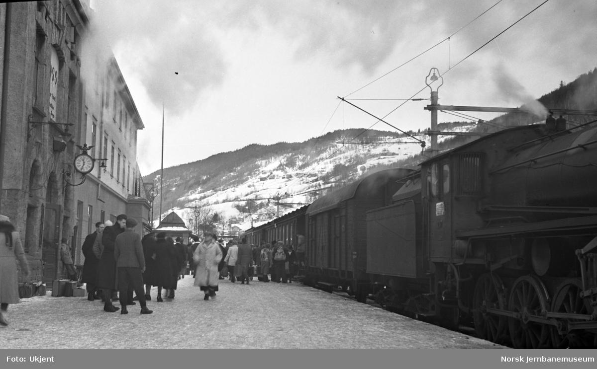 Voss stasjon med reisende og damplokomotiv foran persontog i spor 1