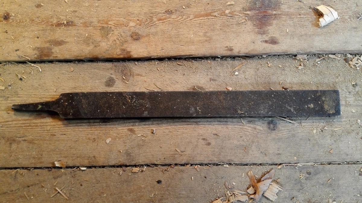 Stor flat rasp eller trefil, rund på den eine sida og flat på den andre. Begge sider har middels grovt riflemønster, det same har den eine kantsida, medan den andre er glatt.