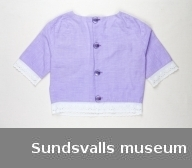 En lila blus med vit brodyrkant i ärmsluten och i nederkant. Blusen knäpps i ryggen med fyra stora plastknappar.