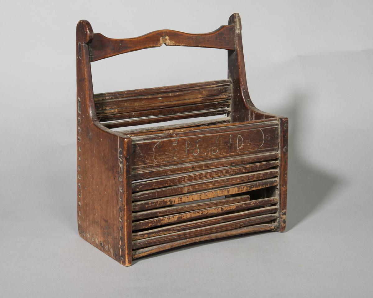 Skekass, stående rektangulär, av trä för förvaring av skedar. Hela kortsidor och fram- och baksida av smala ribbor. Kortsidorna går upp i ståndare som är förbundna med intappad skulpterad tvärslå, som utgör bärhandtag. Upphängning på väggen. Enligt kataloglapp är gavlarna av bok, handtaget av björk och ribbor av furu. Rester av brun färg.