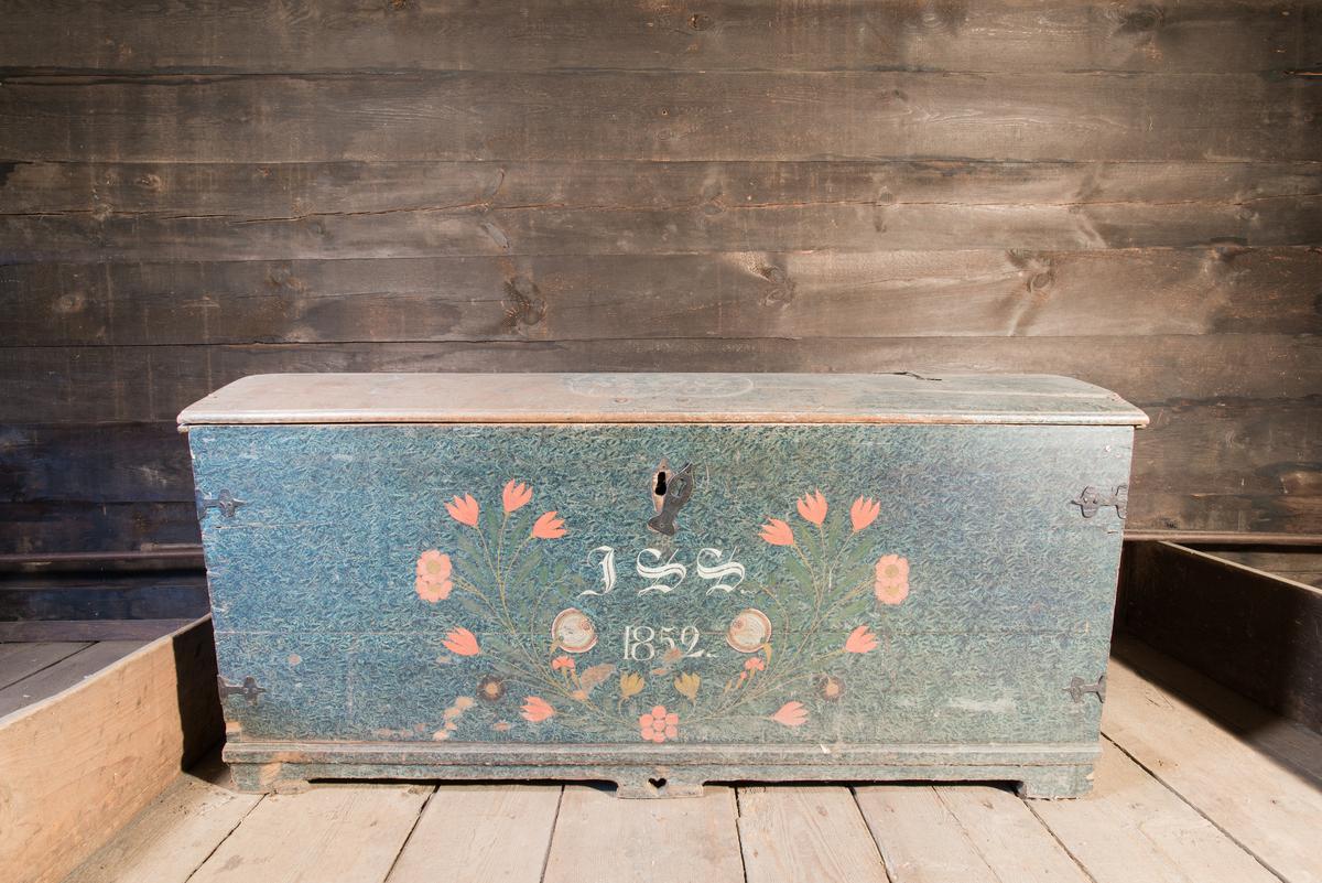Pjaltakista av furu. Rektangulär med svagt välvt lock. Skuren dekor på lockets ovansida och målad dekor utvändigt och invändigt. Invändigt läddika till höger. Bandjärn, bärhandtag och nyckelskylt av järn. Blå marmorerad bottenfärg med initialier på framsidan i ett bågformigt blomstermåleri med tulpaner, nejlikor, nyponrosor med flera blommor. Ovansidan rester av blågrön bottenfärg med inskurna initialier i en kartusch krönt av bladornament. Invändigt vitmålad med på locket diagonalt ställda linjer av ringar och streck inskrivna i cirklar samt verstext i svart frakturstil.