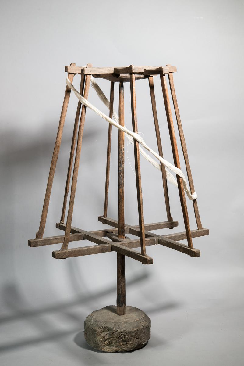 Nystvinda av trä med 8 ståndare fästade upptill och nedtill på horisontella stag. Nystvindan fäst på mittstolpe, fäst i fotkloss. Nystvindan går att snurra.