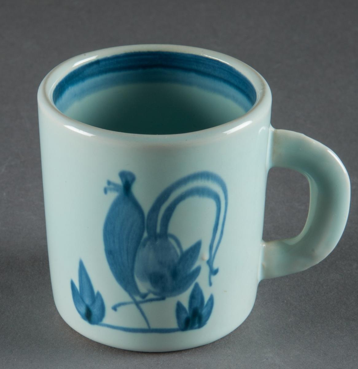 """Mugg med handtag tillverkad vid Bo Fajans. Formgiven av Allan Ebeling, både form och dekor, s k """"tuppdekor"""". Blå handmålad tupp mot ljust, blå botten."""
