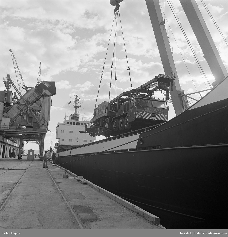 Lastebil lastes fra eller på skip med kran.