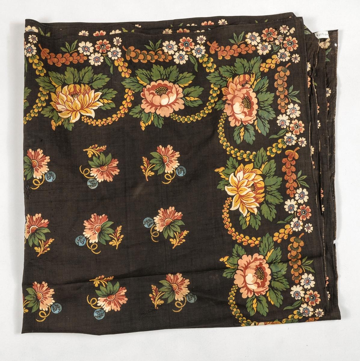 Tørkle i bomullstøy, brunsvart i botn med trykt mønster i blått, gult, grønt, beige og brunt. Falda for hand i to sider, jarekant i dei to ande.
