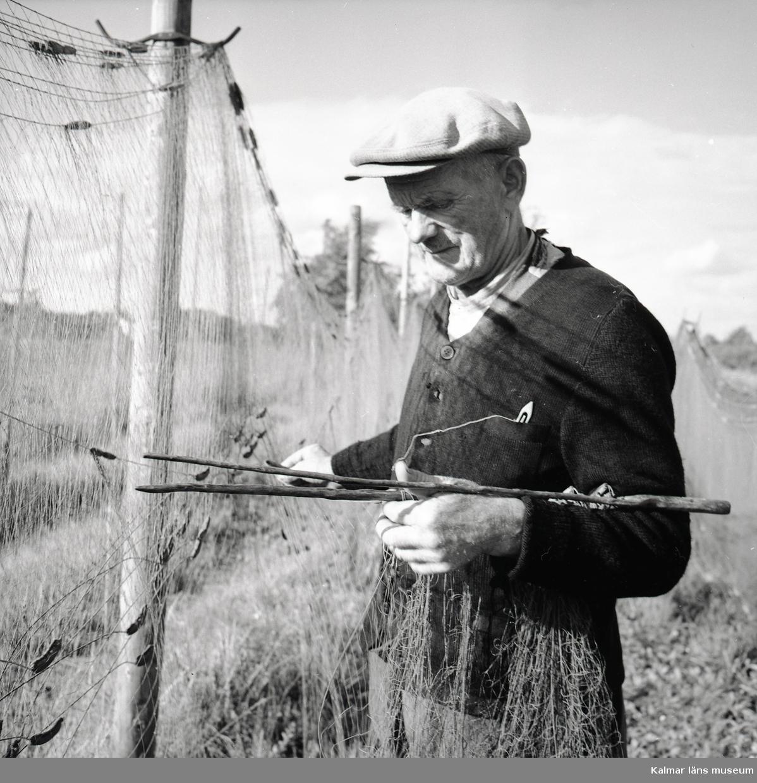 Karl Johansson arbetar med fiskenät vid Stensö fiskeläge.