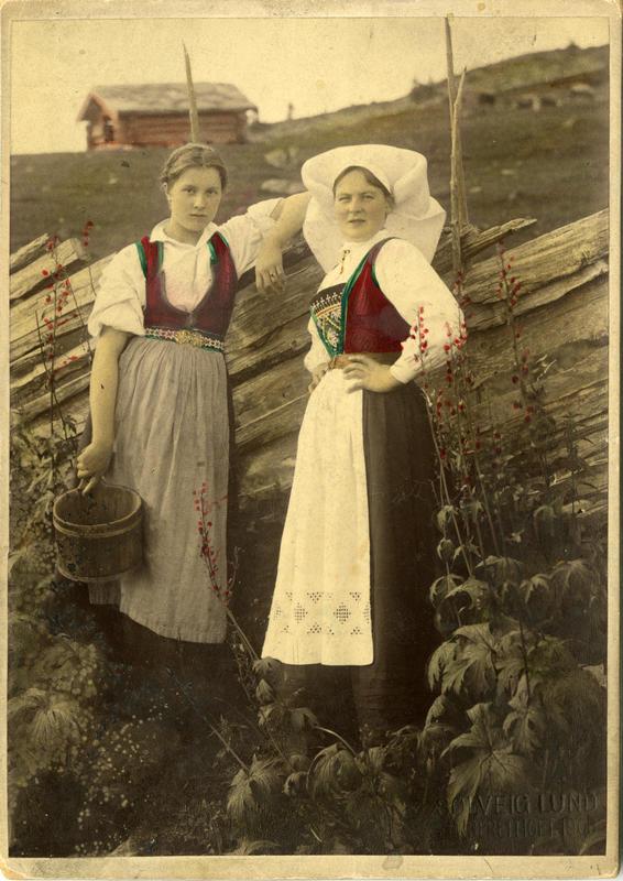 Kolorert fotografi av to kvinner med Hardangerdrakt foran et gjerde på seteren. 1908. (Foto/Photo)