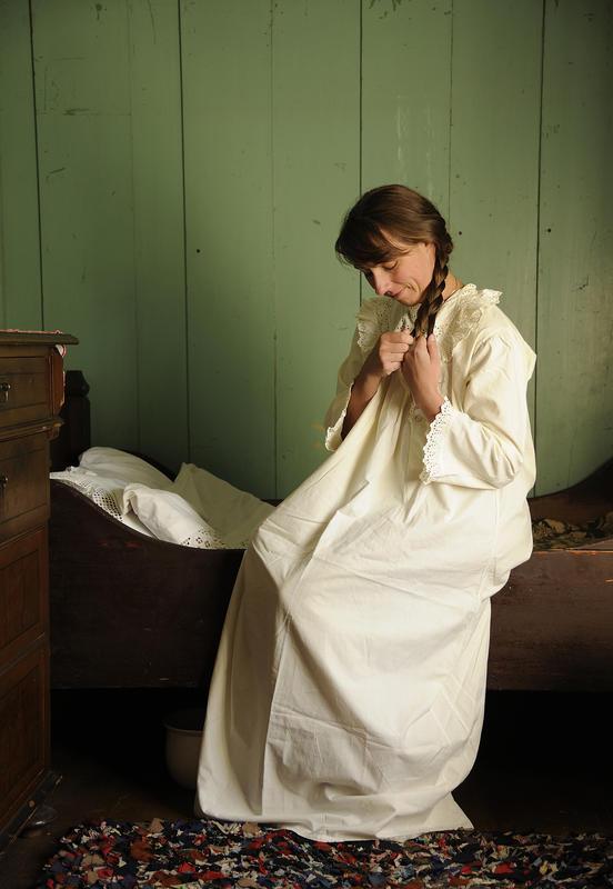 Kvinne med langt hår sitter på sengekanten med en fotsid, hvit nattkjole og fletter håret sitt.