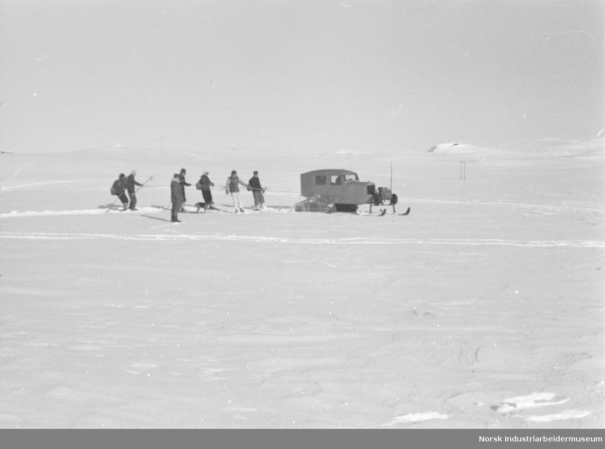 Snø cat (weasel) med folk på ski på slep.