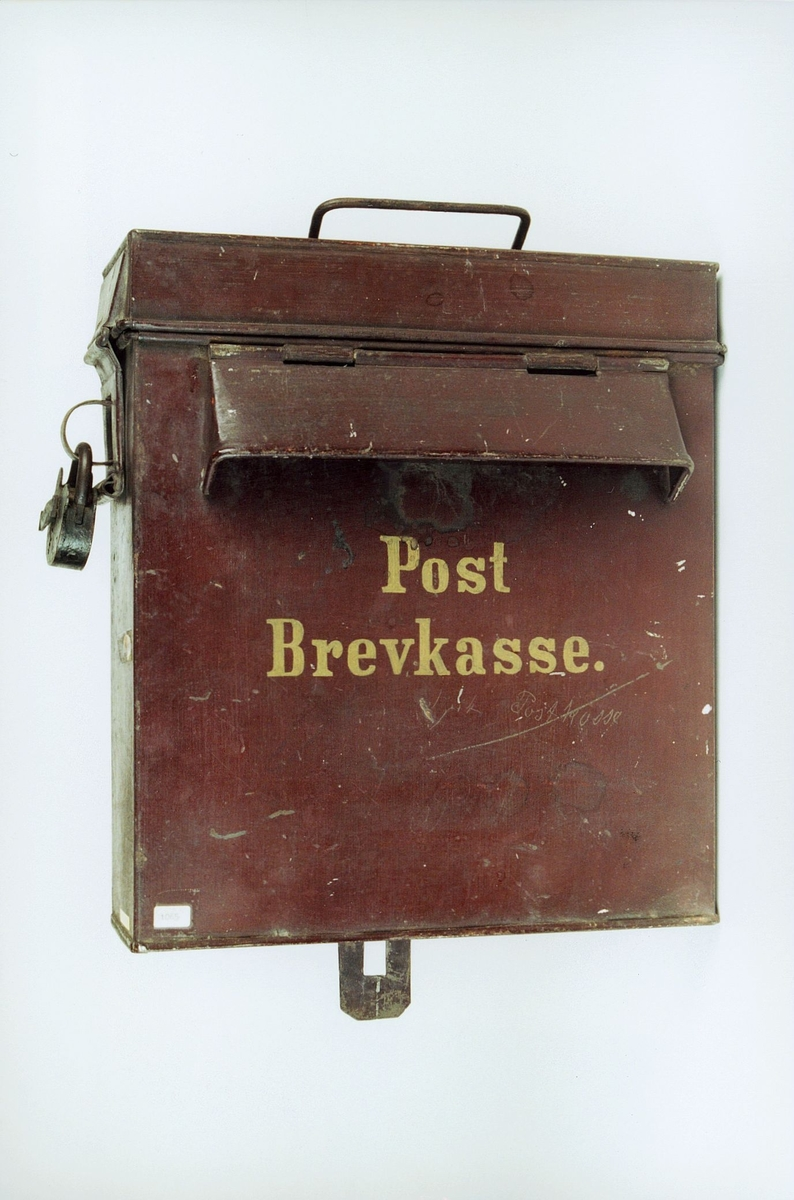 Brun postkasse med gule bokstaver. Kassen tømmes fra toppen. Kassen har hank og lås; ingen nøkkel. Påmalt: Post Brevkasse.