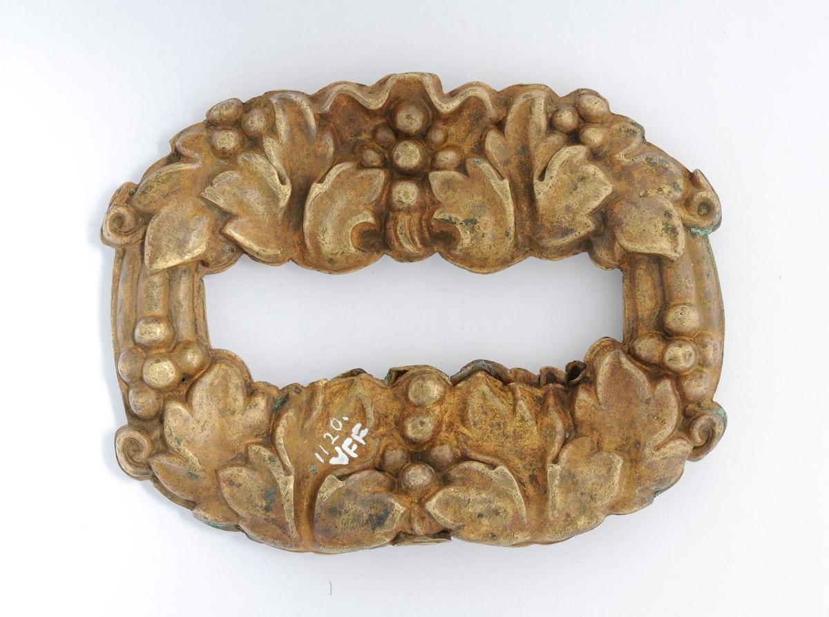 Pynteting av bronse, støypt i to like stykker som er lodda i saman. Lite hol på kvar langside.