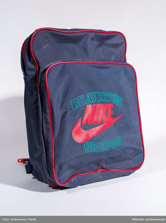 Ryggsäck av gråblåplast med tryck Beaverton Nike Oregon på framsidan. I ytterfacket finns två mindre fack. Använd 1986-1990 av Linus Hansson (idag Rubin) till/från Sinntorpsskolan.