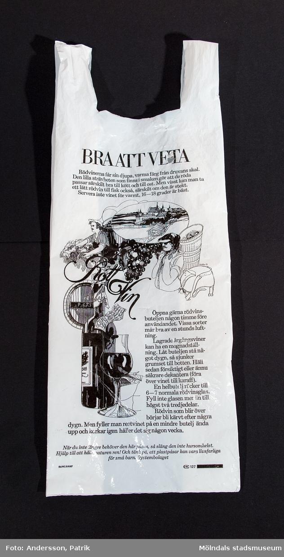 """Plastpåse från Systembolaget med tryck på framsidan: """"BRA ATT VETA"""". Under rubriken finns en stor illustration samt text om rödvin. Längst ner står text om att hålla naturen ren. Tryckkod: SV.PAT.209307 samt AB 127. Kassen användes 1978-02-03 av givaren som då bodde i Lindome."""