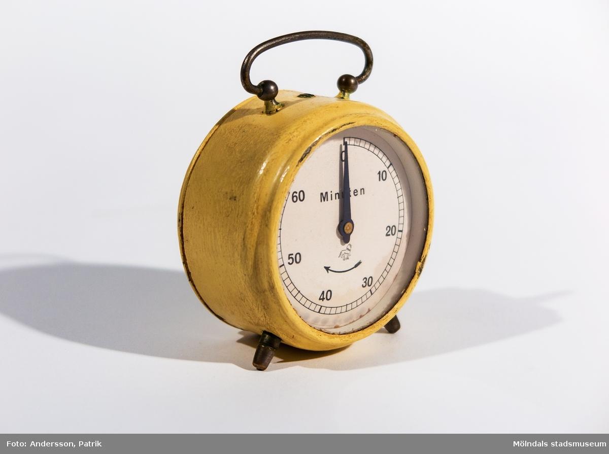 """Äggklocka för tidsmätning vid bl a matlagning. Rund, handmålad, beige klocka. Två små fötter framtill och hänge upptill av metall. Vit urtavla med svarta siffror. Minutindelning är markerat samt siffrorna 0-60 var 10:e steg. På urtavlan står """"Minuten"""" samt en böjd svart pil, riktad åt vänster, som visar urets vridriktning. På baksidan sitter en vridknapp."""
