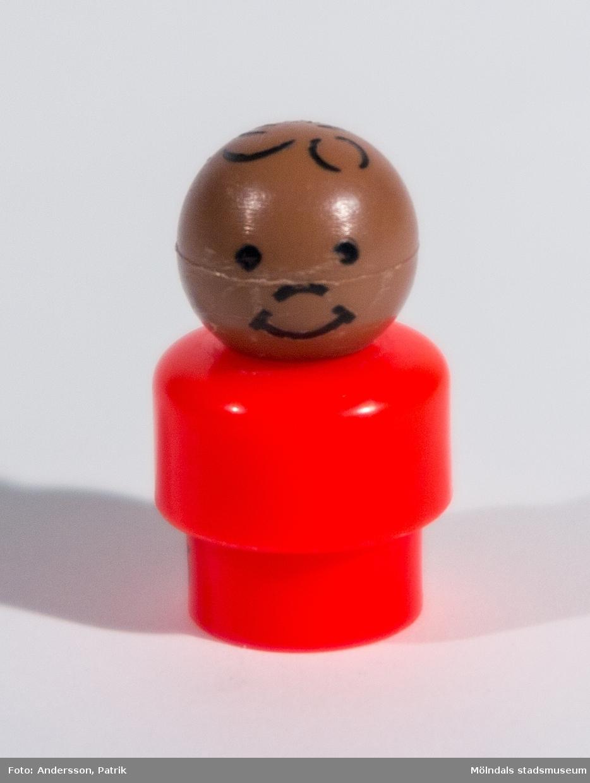 """Rund, röd plastfigur tillhörande Fisher-Pricegarage från 1970-talet. """"Kroppen"""" består av två delar varav den nedersta är smalare för att passa ihop med tillhörande leksaksbil. Ihålig underifrån och längst in är """"huvudet"""" fastskruvat. """"Huvudet"""" består av en plastkula som är målad med hår, ögon, näsa och mun. Inköpt 2001 på Second Hand av givaren, vars barn har lekt med det."""