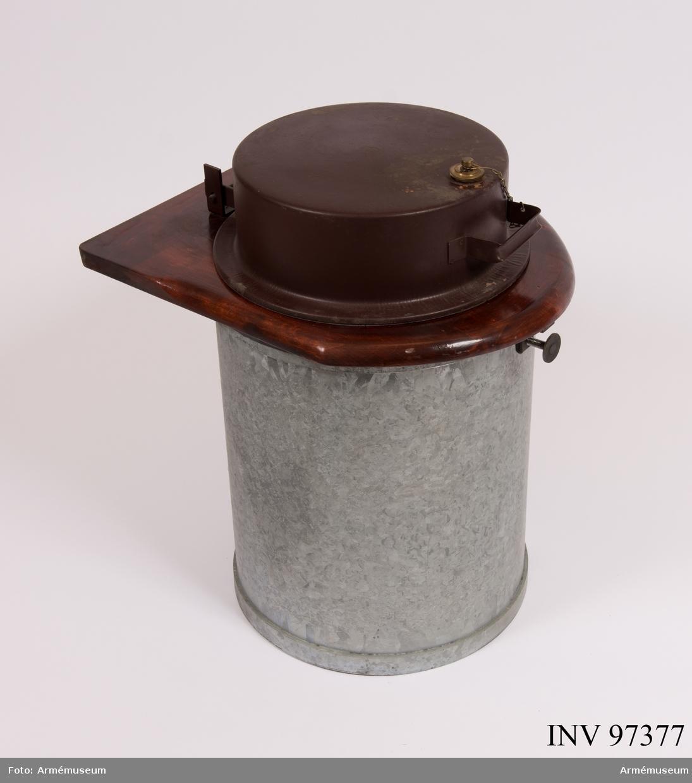 Torrklosett i metall med träsits. I klosetten finns rester av tidningspapper.
