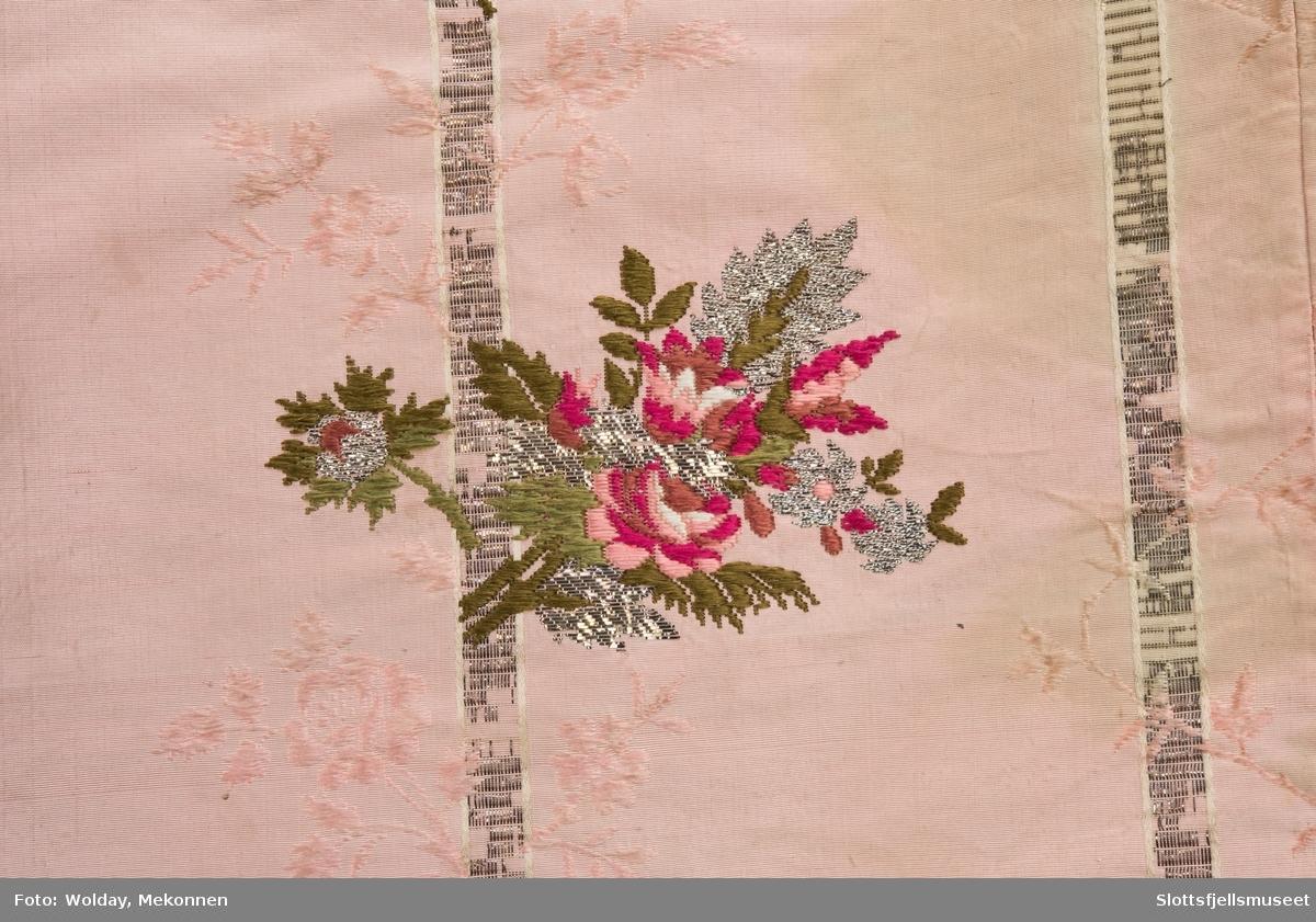 """Dåpspose med hette: Ganske vid """"pose"""" med avrundet slep. To store legg på hver side av halsåpningen,. Innfelte stykker i sidene. Stor hette sydd i ett med posen med søm midt oppe på hodet. (Antakelig omsydd av kjole). Stoff: Rosa silkebrokade med brósjert mønster i rødt, rosa, hvitt, grønt og sølv. Kantet med metallknipling (sølv) omkring hetteåpningen og langs nedre kant."""