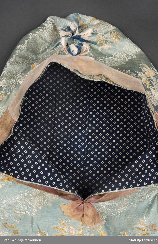 Brosjert damaskvevet stoff i svakt blått med hvite og gylne ornamenter. Fôret m blå bomull m/ hvite romber. Stoffet er sydd sammen så det danner en hette, rynket sammen på toppen. Fôret med mørkeblått bomullstoff mønstret med hvite firkanter. Mørkeblå frynse nederst i kanten. Åpningen foran er pyntet med lilla (nå falmet) band i moiresilke, nederst rester av rosa silkeband. På toppen to rosetter.