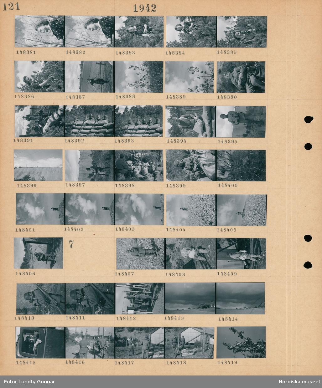 Motiv: (ingen anteckning) ; Porträtt av en kvinna på en äng, en kvinna vid ett staket, en grupp soldater i ett skyttevärn av sandsäckar, en man troligen fotograf Gunnar Lundh staplar sandsäckar, troligen ett sandtag, en soldat står på en kulle.  Motiv: (ingen anteckning) ; Porträtt av en soldat, en soldat med en kamera, två soldater bär en låda, landskapsvy med åkrar och ovädersmoln, en soldat sitter i en bil, soldater går på ett järnvägsspår bärandes ved, soldater med ved vid ett stängsel framför ett nybyggt hus, en blommande trädgren.