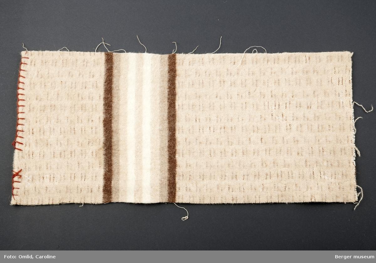 Teppe med bomullsrenning med enkelte innslag av mørkebrune tråder. Bord av mørkebrunt, mellom- og lysebrunt, offwhite i striper.
