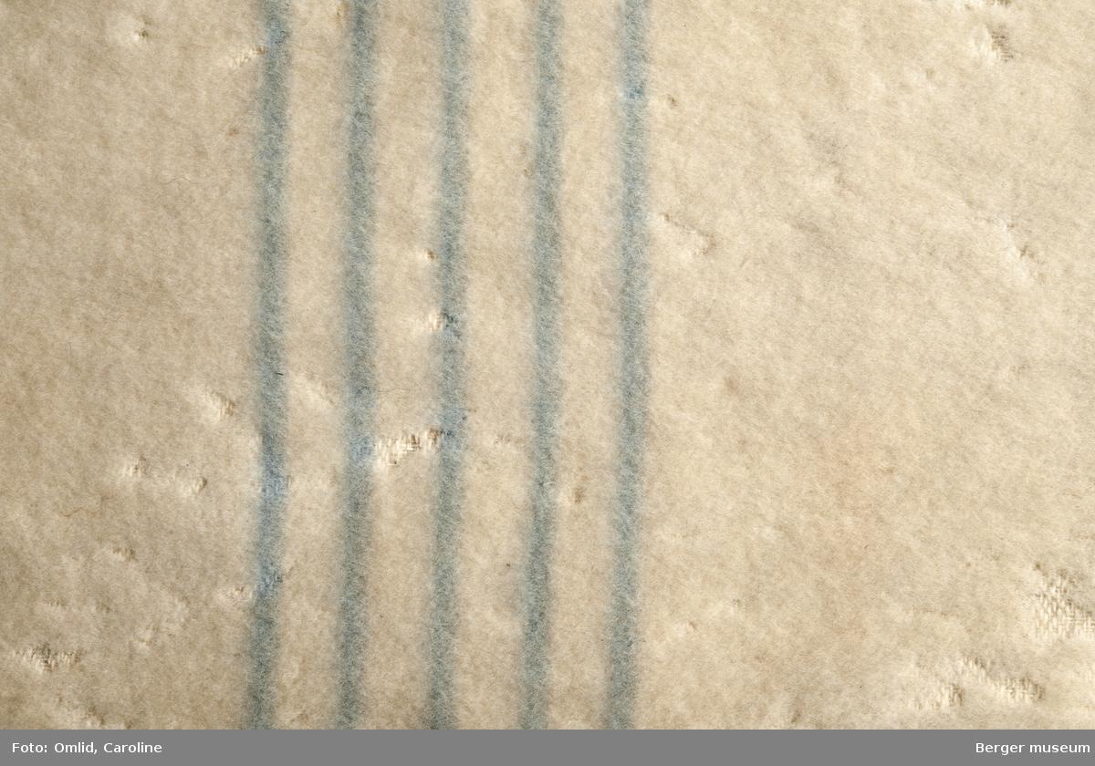 En prøve. Ensfarget, hvitt teppe brutt av bord i femlysblå striper.  Litt skitten, noe møllangrepet.