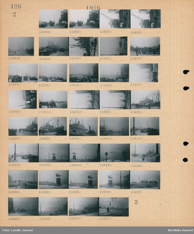 Motiv: (ingen anteckning) ; Människor arbetar vid en järnvägsvagn vid en lastkran i en hamn, lastbilar i en hamn, cylar med ett fartyg i bakgrunden, en grupp män drar en kärra lastad med säckar, ett fartyg, en spårvagn, fotgängare på en bro.