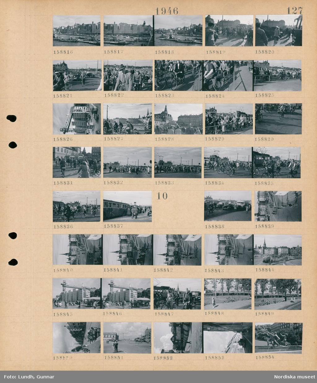 Motiv: (ingen anteckning) ; Stadsvy med fartyg - båtar och bebyggelse, stadsvy med cyklister och bilar, vy av Katarinahissen, cyklister och spårvagn.  Motiv: (ingen anteckning) ; Stadsvy med cyklister - bilar - spårvagn och buss, vy över Katarinahissen, människor på en järnvägsperrong och en ko som betar, lastcyklar, en skulptur.