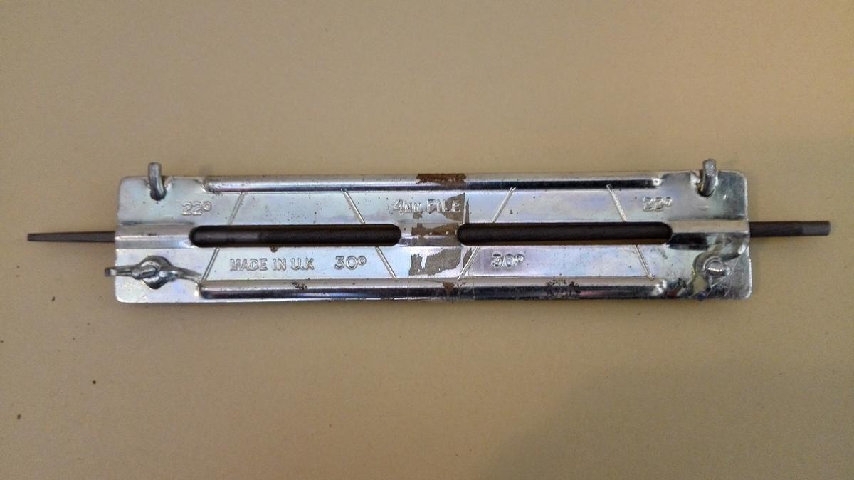Finmønstra rundfil, festa for oppbevaring med augneskruer til ei metallplate.  På metallplata er det markert 22 grader og 30 grader, at dette er ei 4 mm fil, og at den er MADE IN UK. Fila har ikkje skaft.
