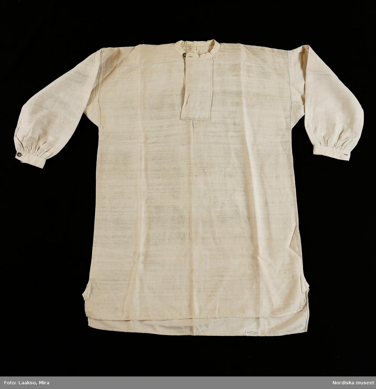 Mansskjorta av halvlinnekypert, med varp av bomullsgarn och inslag av lingarn.Maskinsydd. Ett bålstycke med sidsprund med steglappar av bomullslärft. Axelok, sprund fram med 10 cm bretrt förslag, ståndkrage av bomullslärft knäppt med en vitmetallknapp och tränsat knapphål. Vidsydd ärm med ärmspjäll, rynkad nedtill mot 3,5 cm bred ärmlinning av bomullslärft, med sprund knäppt med  likadan vitmetallknapp. Vanlig skjortmodell under 1800-talets senare del. /Berit Eldvik 2010-07-02