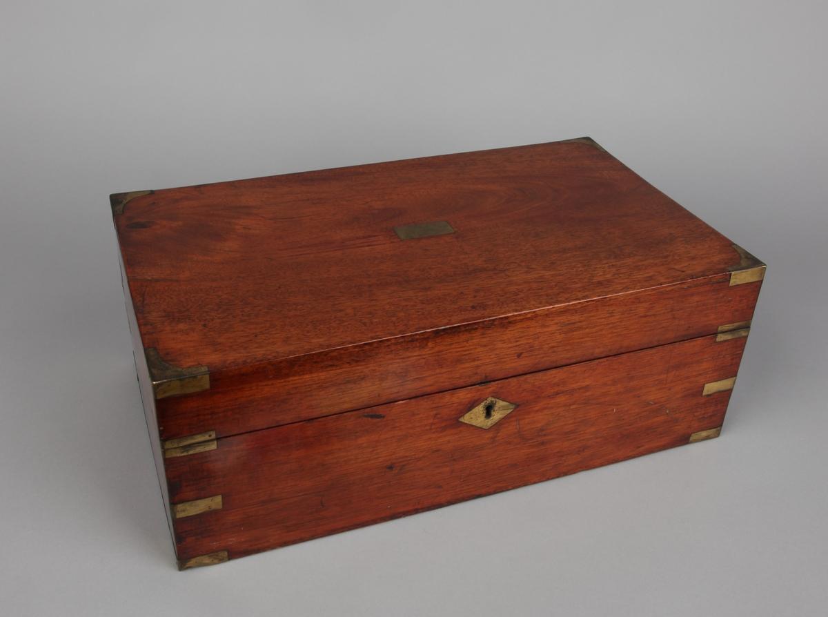 Skriveskrin, rektangulært i mahogny med beslag i messing. Med lås, men nøkkel mangler.