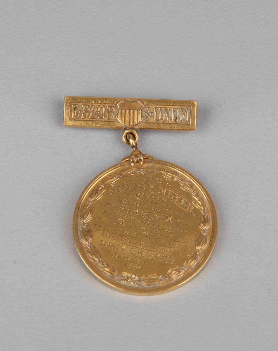Rund gullmedalje med nål med motiv av kvinnehodeog tekst på forsiden samt tekst på nålfeste og baksiden.