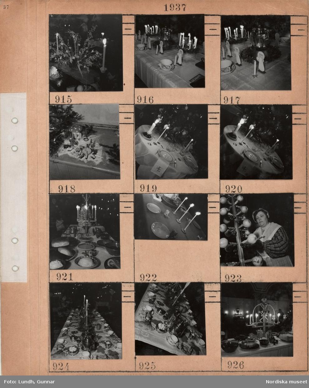 Motiv: Julprydnader, ljusstakar med tända ljus, dukat kaffebord med vit damastduk, luciafigurer, stor kaffepanna, tomtelandskap med tomtar, djur, hus, snö, litet runt bord med broderad vit duk dukat för två, liten pyntad gran, stort rektangulärt bord med vit duk dukat med äldre keramikfat, ljusstake med fot i form av hästar, bröd, smör, frukt, bord dukat med torkad frukt och nötter, nötknäppare, kvinna klädd i husmorsdräkt vid stake med påträdda äpplen, rektangulärt dukat kaffebord med lussekatter, pepparkaksfigurer, brännvinsplunta.