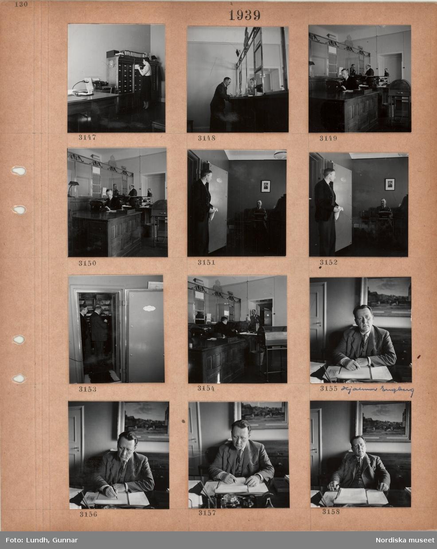 Motiv: Interiör kontorslokaler, kvinna står vid ett skåp med kortregister, skrivmaskin, en man står vid en disk med kassaluckor, två män bakom disk med luckor, skrivbord, skrivmaskin, telefon, en man står i dörren till ett kassavalv(?), en man sitter vid en skrivmaskin, två män står i ett kassavalv, en man, Hjalmar Engberg, i kostym med väst, sitter vid ett skrivbord med block och penna.