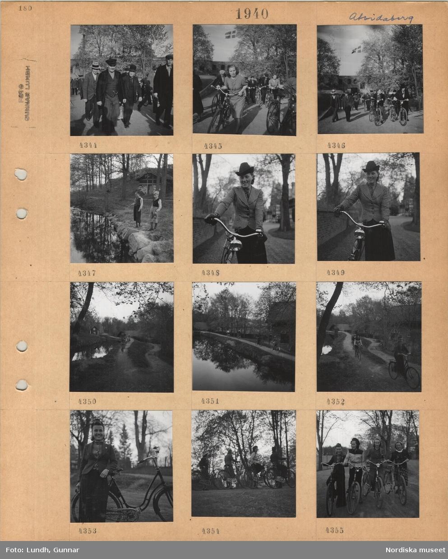 Motiv: Åtvidaberg, män och kvinnor som går på en väg, personer som leder cyklar, hissad svensk flagga på byggnad, , två pojkar metar vid ett vattendrag, kvinna i dräkt och hatt håller i en cykel, cyklande personer längs fabriksdamm, kvinna i kort jacka och långbyxor lutad mot en cykel, fyra fritidsklädda kvinnor med cyklar.