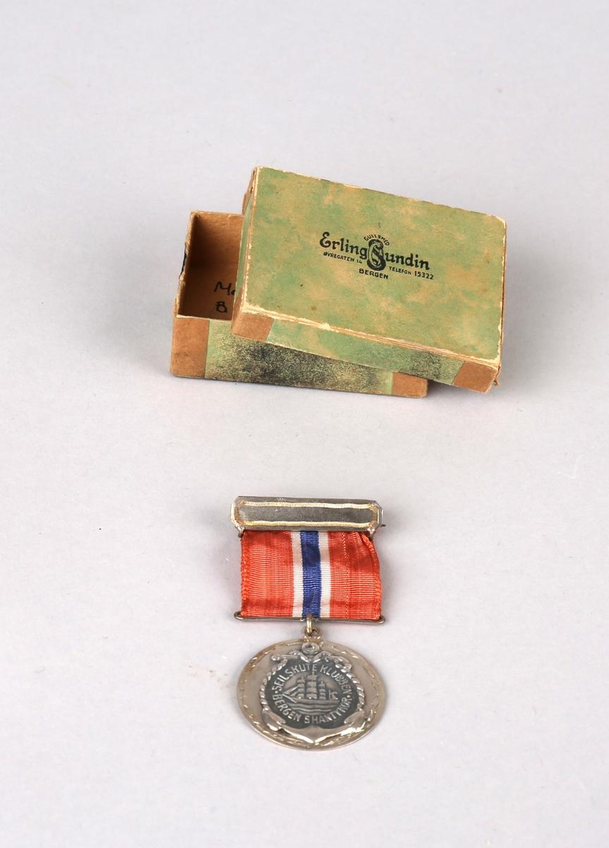 Rund sølvmedalje med bånd og nål. Ligger i liten pappeske med løst lokk. Med motiv an en seilskute omkranset av anker og tau.