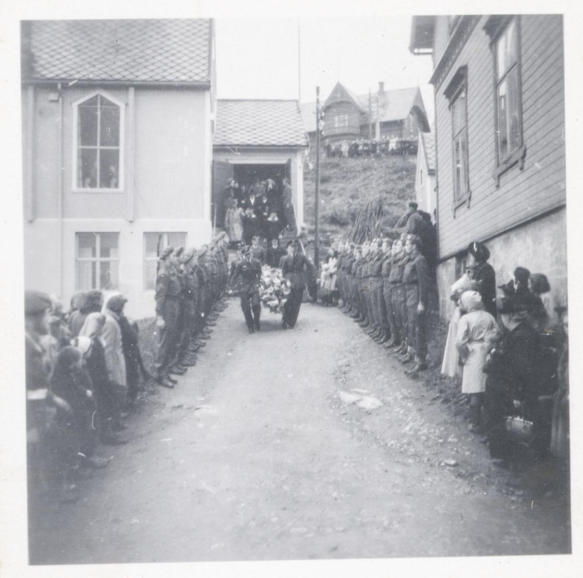 Fire offiserer bærer en blomsterpyntet urne ut fra Bethel i Harstad.