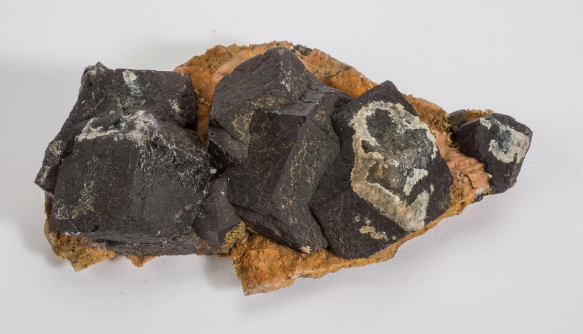 Xls, sortfiolett, rombedodekaedre på rødbrun matriks, hyalitt.