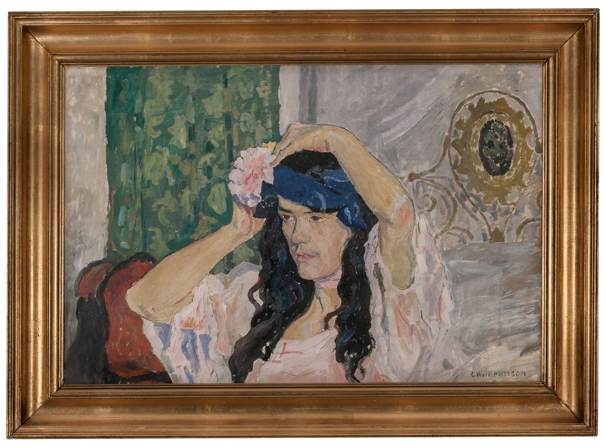 """Oljemålning på duk, """"Bailarina"""" av Carl Wilhelmson. Bröstbild av en kvinnamed blåsvart hår, som med båda armarna lyftade fäster en blomma i håret. Fonden grå med grönt draperi. Förgylld ram. (Kat.kort)"""