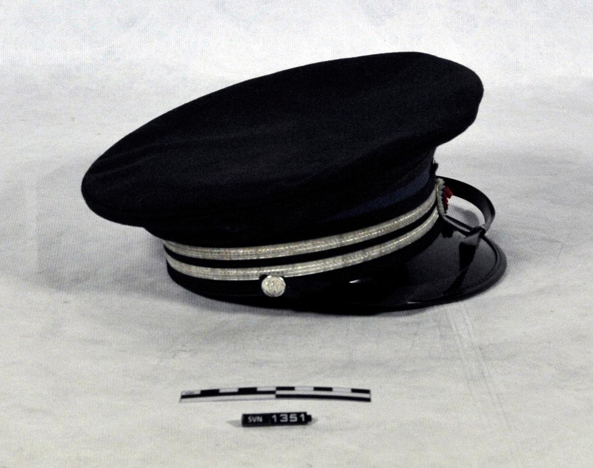 Sort/mørk blå uniformslue fra NSB. Luen har skygge, og hakestropp. Rundt luen er det to sølvfargede striper. Midt på lua forran er det en rosett som er lagvis (fra ytterst til innerst) Hvit, blå, røde. Midt på luen, på baksiden er det en NSB logo.