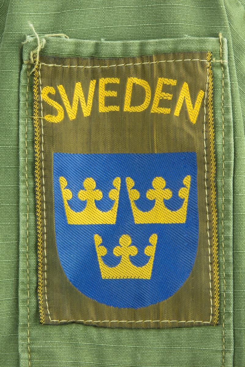 """Vapenrock av modell m/61.  Vapenrocken är militärgrön och brukad vid FN-tjänst. Två bröstfickor fram med dold knäppning. Dold knäppning fram med synlig övre knapp vid halsringning. Slejf på vardera axel för axelklaffhylsor. På vänster axel (framifrån) sitter ett ljusblått tygmärke med FN logga, på höger axel sitter ett tygmärke med Svensk vapensköld och texten """"SWEDEN"""" i gult. Storlek Medium/Regular."""