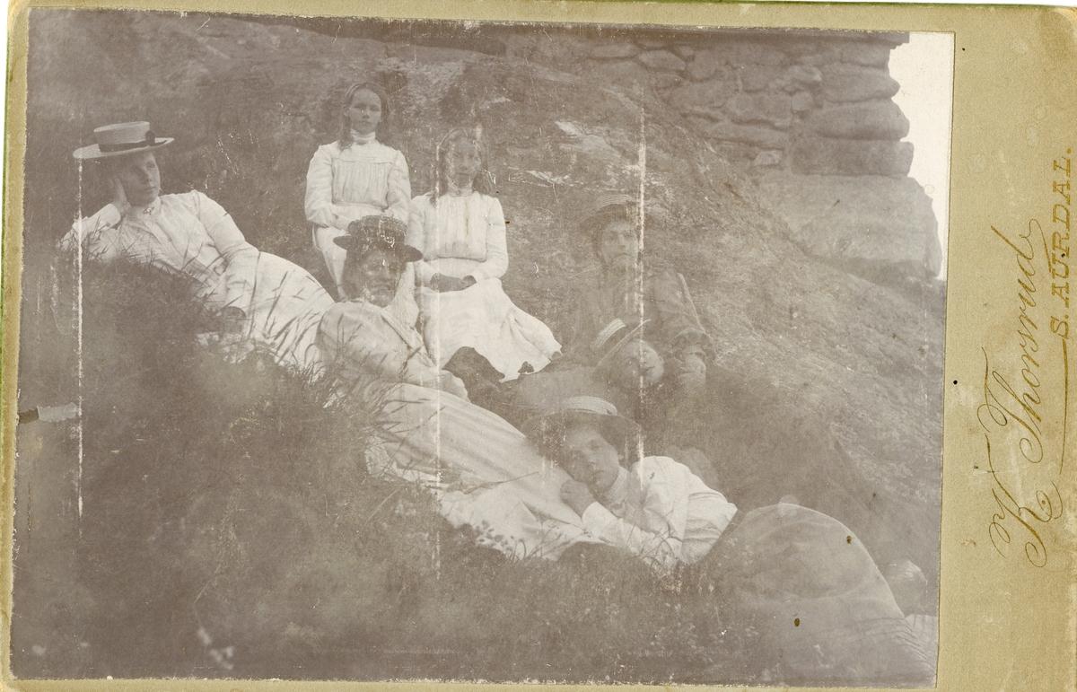 6 kvinner/jenter ligger i graset foran en steinmur.