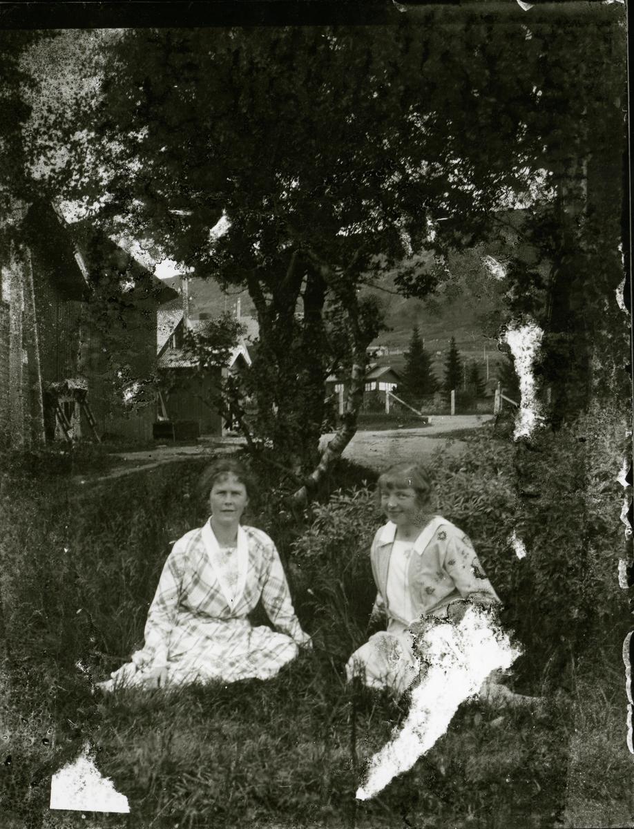 To kvinner sitter i graset foran et tre. Begge har kjoler.