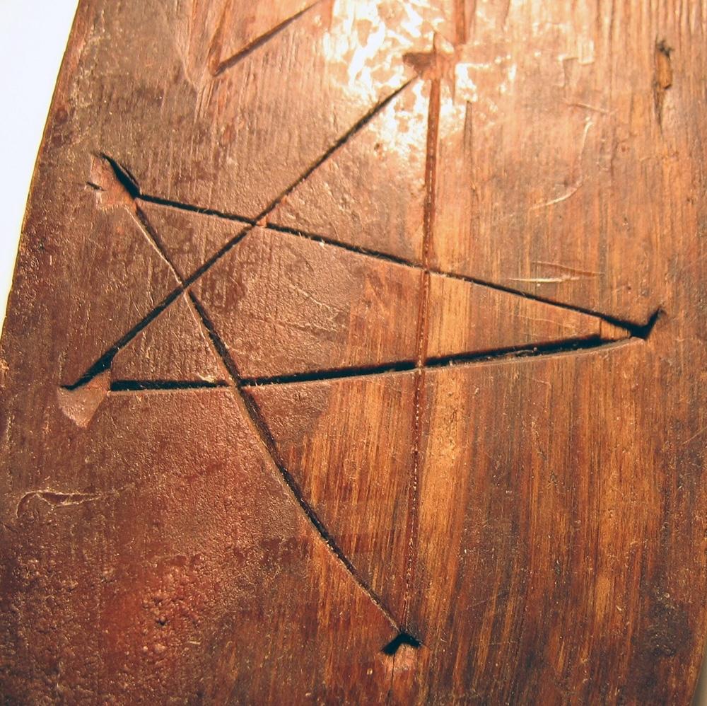 En oval botten till en svepask. Bottnen har fasade kanter. Längs med ytterkanten löper hål efter träpligg. Bottnen är försedd med två bomärken, ett pentagram (stjärna) samt troligen en ofullständig åttabladsros.