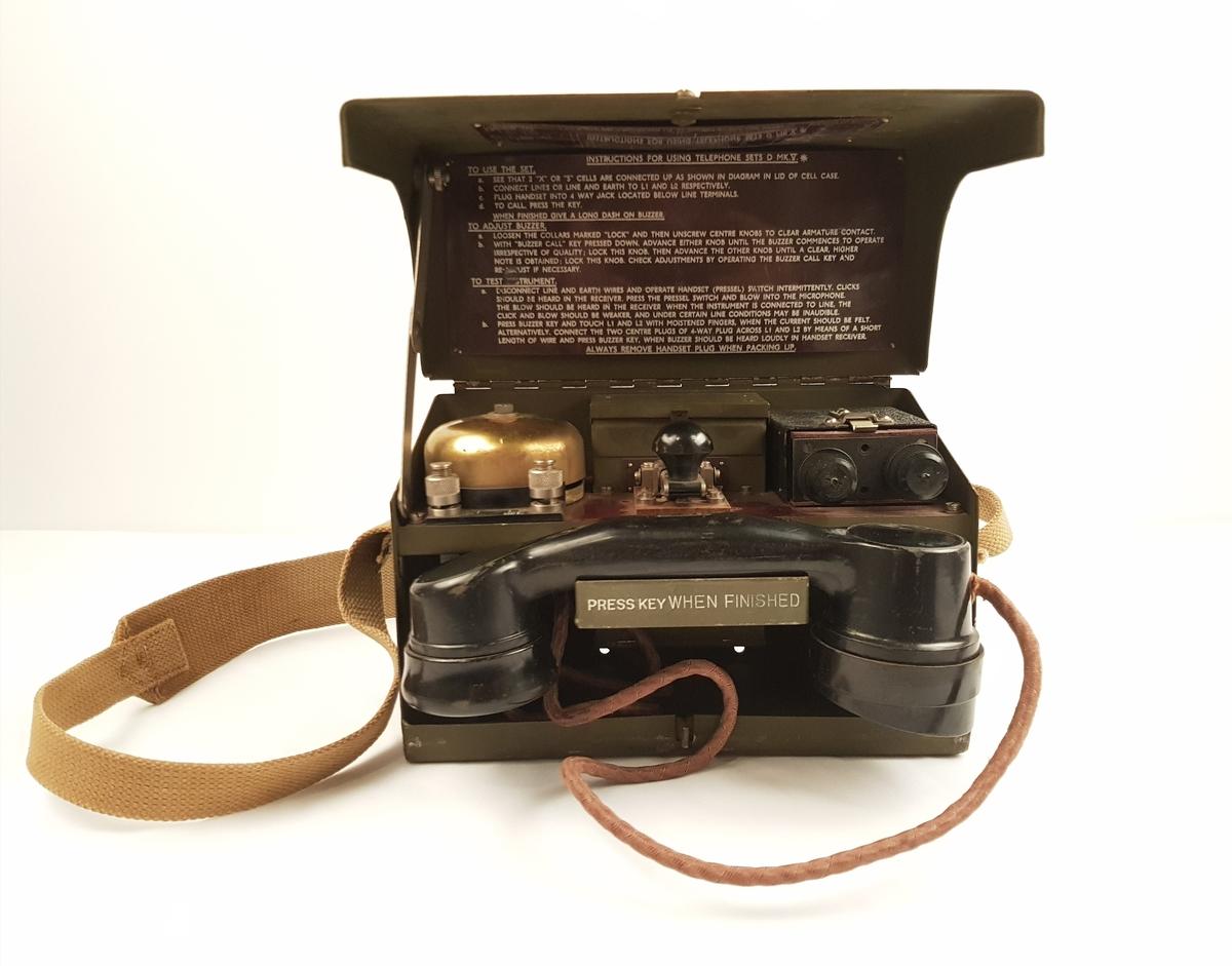 Feltelefon i rektangulær metallboks med bærestropp.