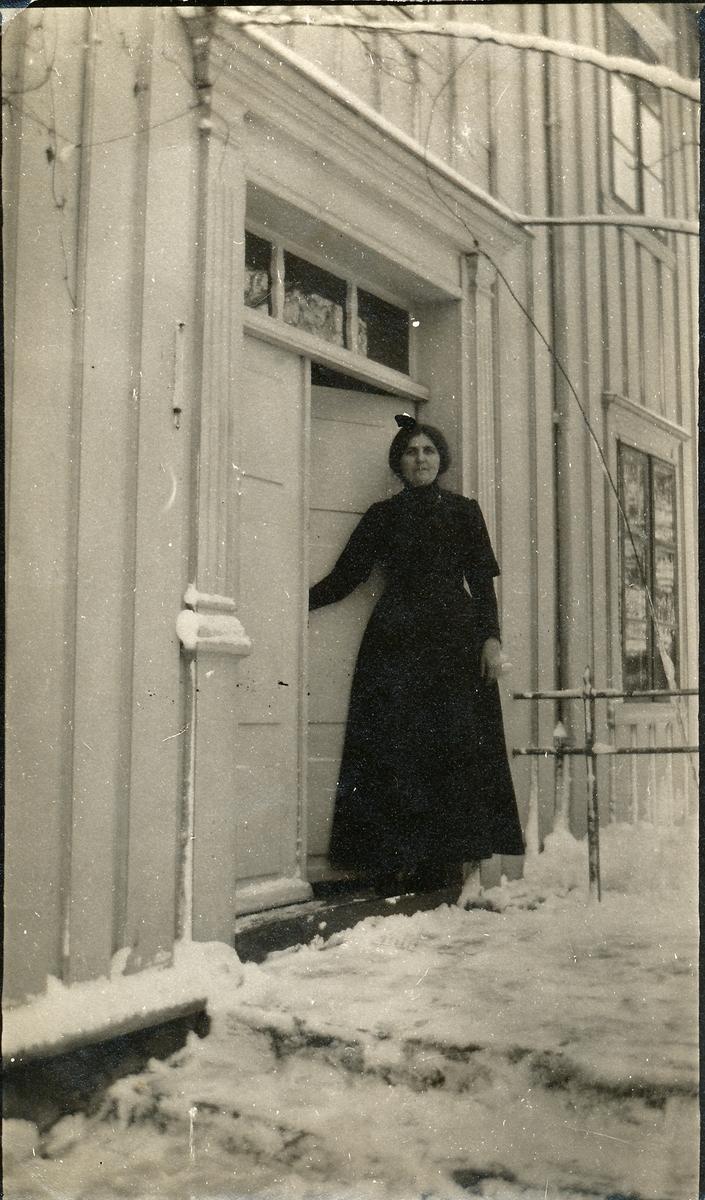 Kvinne står på trammen til et hvitt trehus. Vinter og snø. Holder i døra. Nanna P. Venes på trappa til forretningen sin (på Øver-Mo).