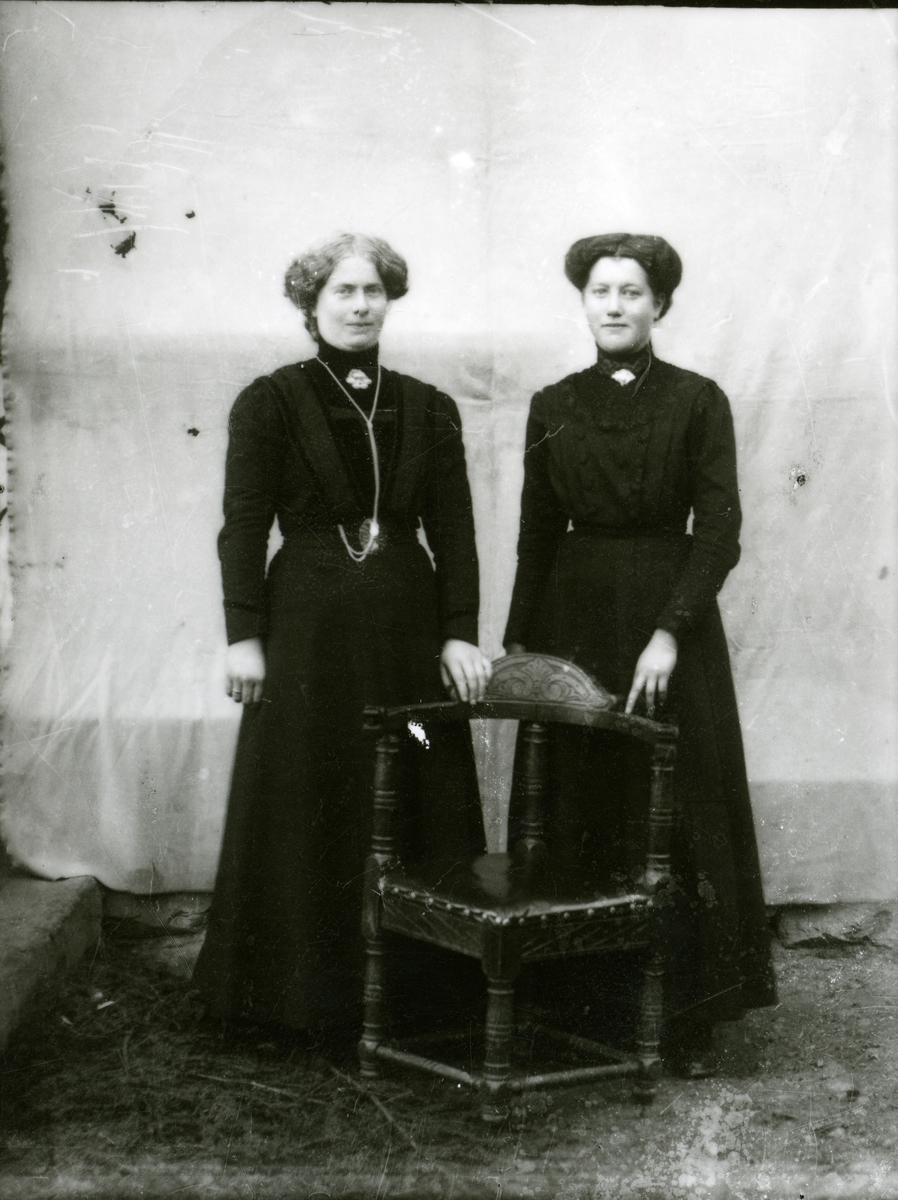To kvinner i svarte kjolar.
