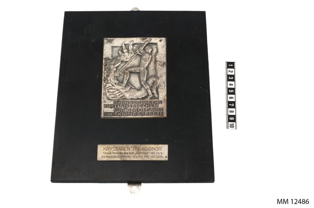 Av silver, på platta av svartpolerad ek. I relief, bild av naken yngling i strid med en eldsprutande drake, därunder följande text: Brandbolagens förtjänsttecken för berömvärt släckningsarbete. På bricka på plattan, texten: Kryssaren Tre Kronor Timber trading den 10/8, Järntorget den 25/8 och magasinkvarteret den 4/9 1947 Göteborg.