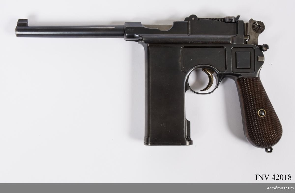 """Grupp E III. Automatpistol modell 1896 för 20 patroner.  Längst bak på pipans översida står system Mauser, på dess vänstra sida ett krönt U. Upptill på kolven är nr 53 instansat. Kolvens ring saknas. Slutstycket märkt med ett krönt U och en krona. Magasinets """"öppningssprint"""" märkt med ett M och en halvmåne /1985-02-07 EW."""